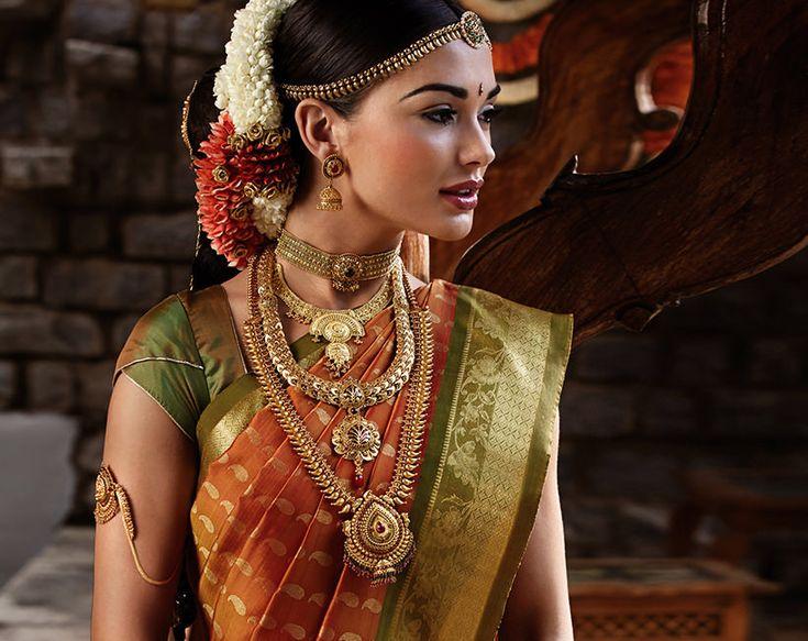 South Indian bride. Gold Indian bridal jewelry. Temple jewelry.Jhumkis. Orange Kanchipuram silk saree.Braid with fresh flowers. Tamil bride. Telugu bride. Kannada bride. Hindu bride. Malayalee bride.Kerala bride.South Indian wedding. Amy Jackson for Tanishq.