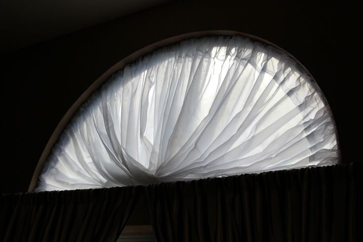 Beautiful covering for a half moon window using only a hoola hoop and two sheer panels.