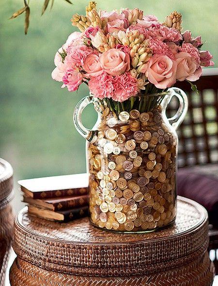 Dentro da ânfora, um vaso menor com água acomoda rosas, cravos e angélicas, camuflados no farto punhado de botões de madrepérola