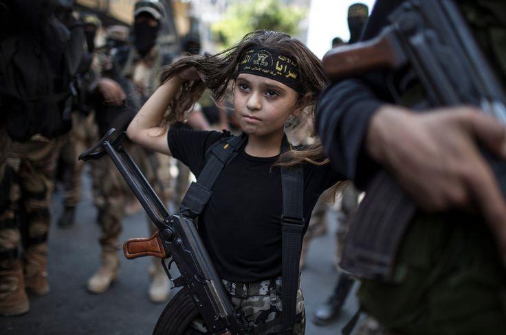 A PALESTINIAN GIRL WITH A KALASHNIKOV RIFLE, AMID MILITANTS IN GAZA CITY