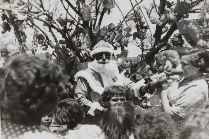 BA1340/ERA5/42C: Father Christmas hands out the presents from the mulga tree in the kindergarten yard, Mt Margaret Mission, ca.1955 https://encore.slwa.wa.gov.au/iii/encore/record/C__Rb4061559