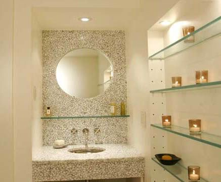 Glass shelf under bathroom mirror adds space without adding bulky look
