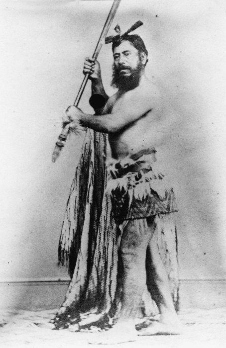 Wirimu Maihi Te Rangikaheke, also known as William Marsh, [ca 1865] He holds a taiaha and a korowai (Maori tag cloak), and wears a feathered piupiu. Photographer unknown.