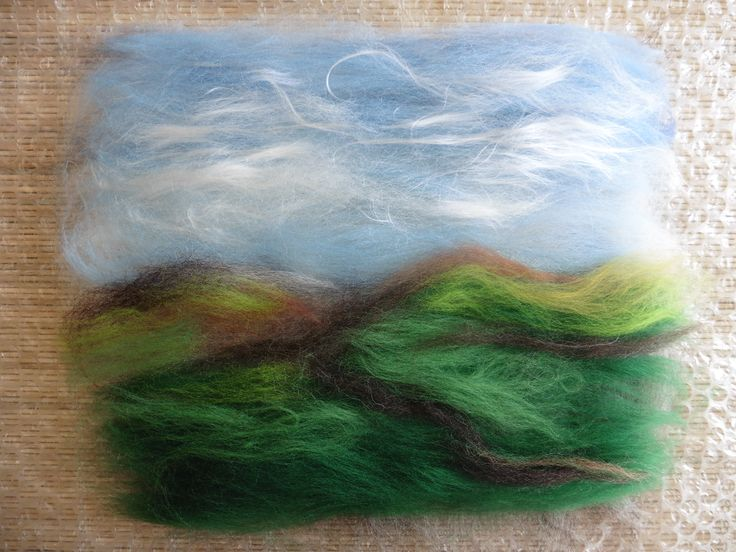 """This is the start of """"Scottish Hillside in Spring"""".  This piece was lightly wet-felted as you see it laid out here; then sheep were needle-felted onto the surface, and eventually the whole thing was felted again. See more work by LittleDeb on Facebook, Folksy and Etsy."""