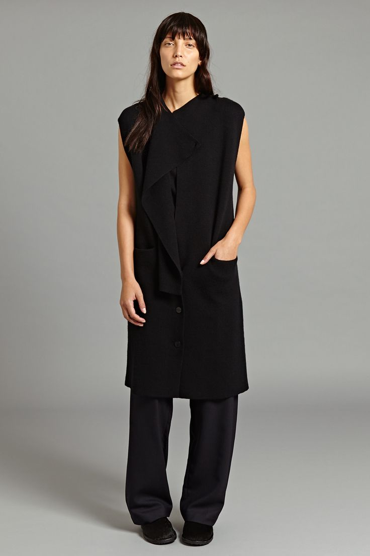 Jota Cashmere Jacket In Black. This sleeveless cashmere jacket is given a distinctive silhouette by an overlapping lapel cut to a right angle at the waist. The jacket fastens with three buttons from the waist down and a smaller button to the side of the neck, which can be fastened for a sleeker look or left open to allow the fabric to cascade.