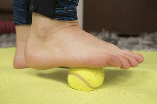 Tennispallon pyörittely jalan alla: Tämä rullausliike venyttää jalkapohjan lihaksia ja lihaskalvoja. Faskioiden eli sidekudoskalvojen hieronta parantaa lihasten elastisuutta. Liian kireät sidekudoskalvot voivat heikentää lihastasapainoa ja lihasten yleistä toimintaa. Jalkapohjan rullaus esimerkiksi tennispallolla on erinomainen kehonhuoltoliike, jolla on yleensä vaikutusta myös pohjelihaksen venyvyyteen. Käytä reilusti painoa pallon päällä ja tunnet, kuinka veri alkaa kiertää jalassa…