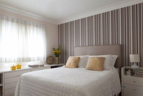 As discretas listras verticais em tons escuros destacam sem excessos a parede da cabeceira desse quarto, que tem lençois e móveis em tons claros. O projeto é de Rodrigo Kolton.