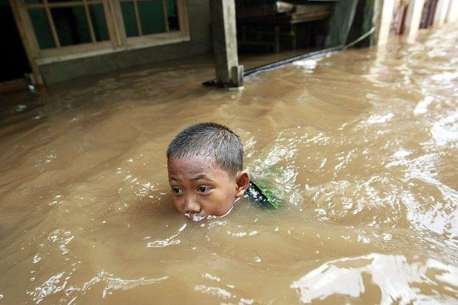A boy swam in floodwaters in Jakarta, January 15, 2013 | © Bagus Indahono | European Pressphoto Agency