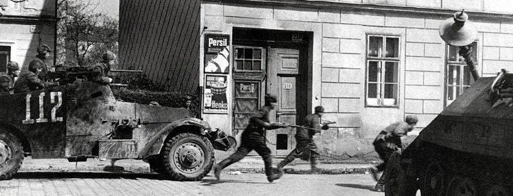 A Soviet Lend-Lease M3 White scout car and infantry move down the streets of Vienna, past a knocked out Sdkfz 251. April 1945. ""