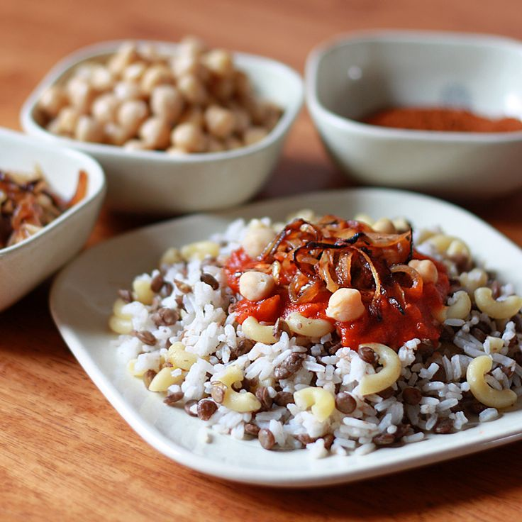 Koshari, the national dish of Egypt.  A flavorful combination of lentils, rice and macaroni topped with a spicy baharat-seasoned tomato chile sauce, garbanzo beans, and crispy fried onions.