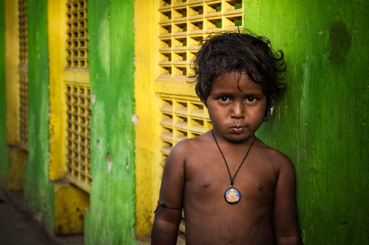 A bright green and yellow wall provides a colorful background for this portrait of a child at a Kolkata railway station in India.