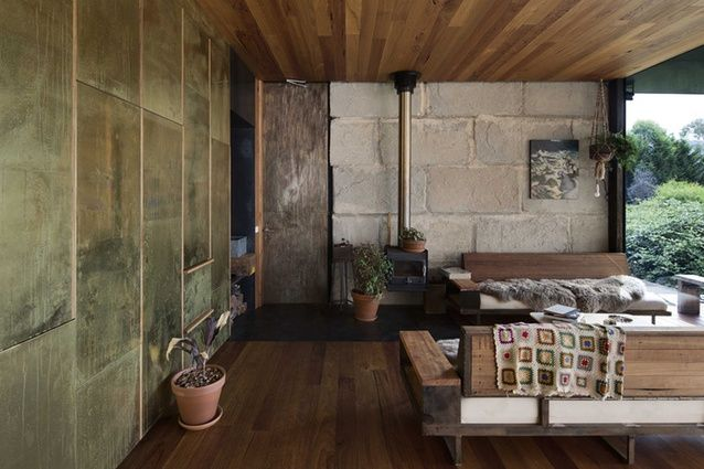 Inside, a mix of brass, timber and overscale blocks of concrete combine with bespoke furniture.
