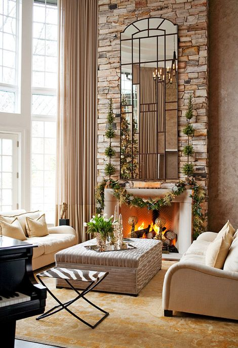 On a towering fireplace made of stacked stones hangs a dramatic mirror that follows the mantel up to the ceiling. The mirror's verticality is also reflected in the cascading draperies adorning the two-story floor-to-ceiling windows.