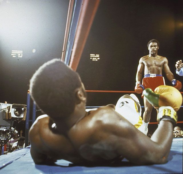 Joe Frazier looks up at George Foreman after being knocked down in the second round of their Jan. 1973 fight in Kingston, Jamaica. Frazier was knocked down three times in the first round and another three in the second before the referee stopped the fight. (Neil Leifer/SI)   SI VAULT: Foreman clobbers Frazier in earning TKO victory (2.5.73)