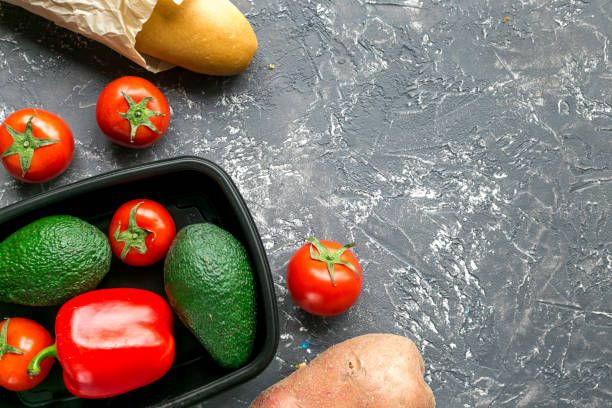 vegetables in plastic tray on gray desk background top view mockup