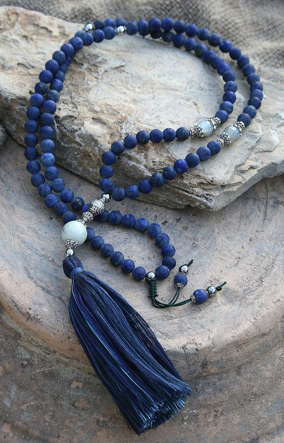 Mala necklace made of 108, 8 mm - 0.315 inch, frosted lapis lazuli gemstones and decorated with faceted moonstone, silver color hematiet and metal bead caps. The guru bead is a 14 mm - 0.551 inch jade stone - look4treasures on Etsy.