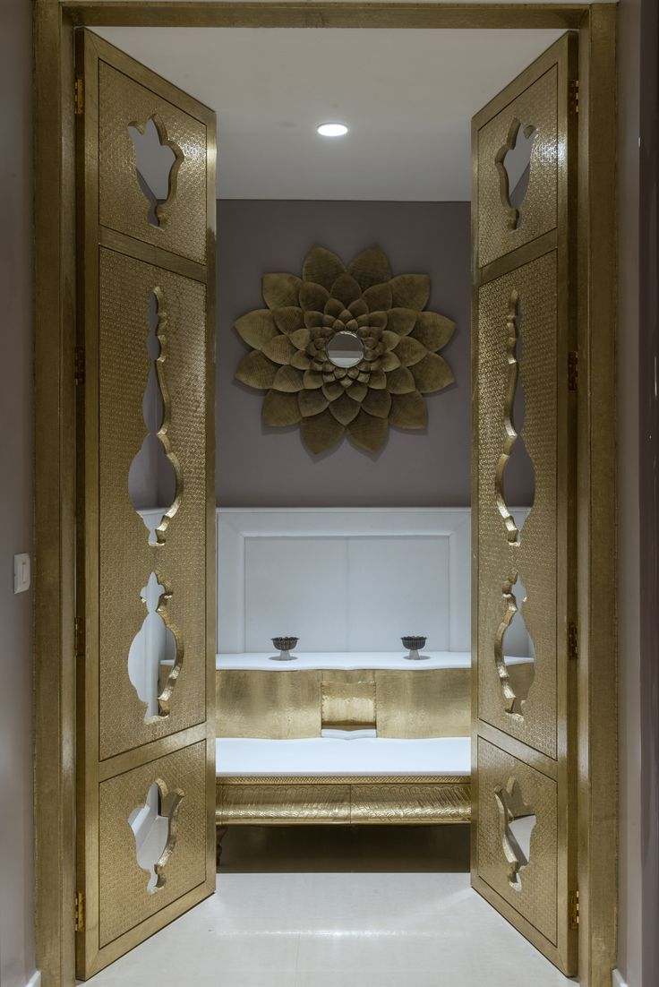 Gateway to serenity , modern version of pooja room set up in brass detailing and white marble .