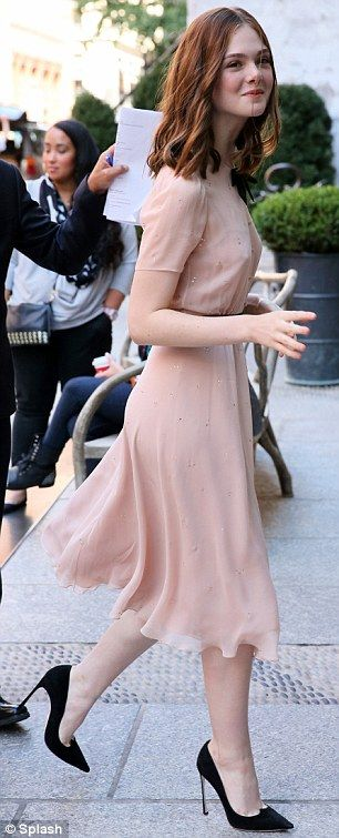 Think pink: Elle's first look was a blush pink dress with a black sash and bow, and matchi...