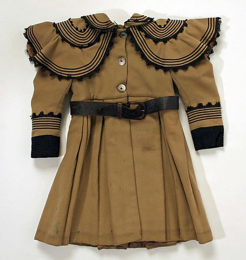 Little Girls' Tan Wool Coat With Black Cotton Trim and Black Leather Belt, Worn With Matching Tan Wool Bonnet With Black Trim, American, 1895-1899