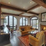 An exposed wood-beam ceiling and large windows dress up the living room of the Villa de Suenos (House of Dreams) oceanfront estate on St. Simons Island, Ga. The gated property has a main house and a pavilion/carriage house separated by a pool and large outdoor entertaining area.  | HGTV FrontDoor