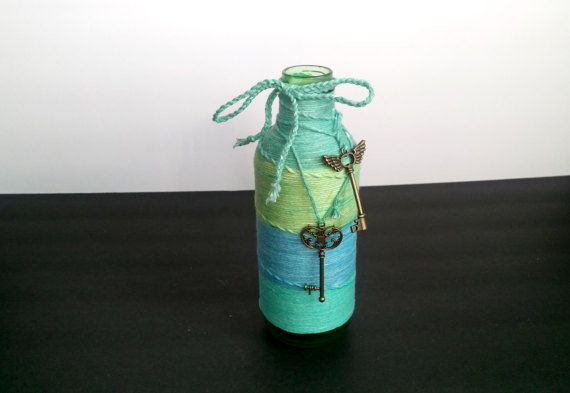This vase is versatile, as it would fit in perfectly to any beach themed home decor or wedding as a centerpiece vase. It is hand wrapped using 100% cotton yarn, and accented with several unique decorations. The vintage-style skeleton keys can be removed with ease, and adjusted to your liking. The bow is hand braided using the same yarn that wraps the bottle. The sea glass inspired bottle is painted by hand and sealed, you can fill it with water for flowers without it washing away easily…