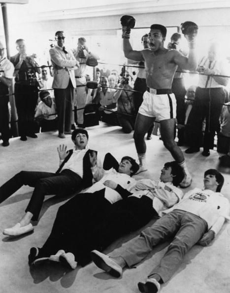 American heavyweight boxer Cassius Clay poses in the ring in mock victory over British pop group The Beatles, 1964.