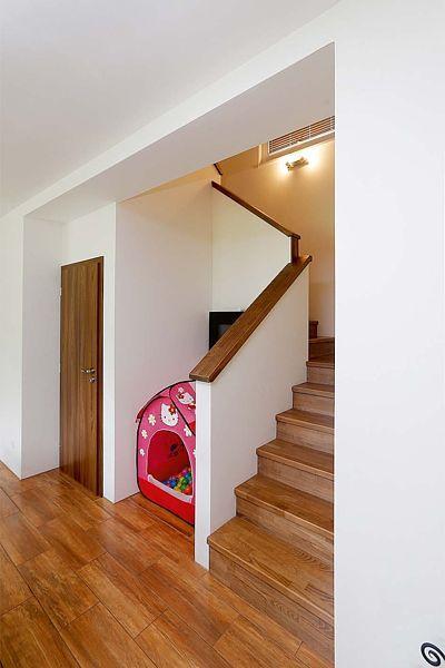 Obložení lomeného schodiště perfektně ladí s dekorem podlahy a dveří.