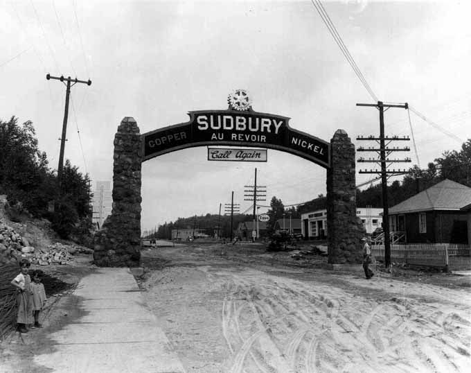 "Gate at the eastern city limits of Sudbury, 1950. -- SOURCE Main Branch. SOURCE Photograph (10"" x 8""). DATE 1950. DATE 1950. SUBJECT Sudbury -- Gates. NOTE Donated by The Sudbury Star, Aug. 17, 1950, p. 24. NOTE Tommy Whiteside Esso station, 1 Coniston Rd.' T.W.'s house right foreground, 661 Kingsway. New pavement being built - finished Aug. 21, 1950. Gate was torn down in summer, 1950. NUMBER MK0472EN."