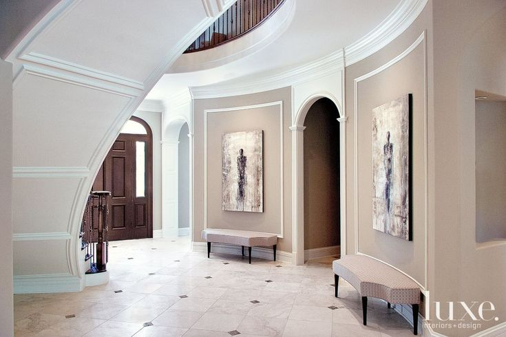 In the entry, a winding quarter-sawn oak-and-wrought-iron staircase by Heritage Luxury Builders leads up to the second floor, which is accentuated by a grand balcony. The silver-leaf-finished chandelier with rock crystal accents is from Holly Hunt.
