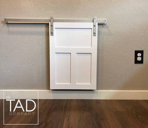 Cover your pet door with this decorative mini barn door. DOOR DIMENSIONS: 24 H x 17W  DOOR COLOR: White  TRACK & BACKBOARD LENGTH: 36  HARDWARE COLOR: Satin Nickel        Mini Barn Door // Tiny Door // Little Door // Tiny Sliding Door // Pet Door // Pet Decor // Dog Door // Cat Door // Farmhouse Chic // Rustic Modern // Decorative Pet Door Cover // Unique Gift // Housewa...