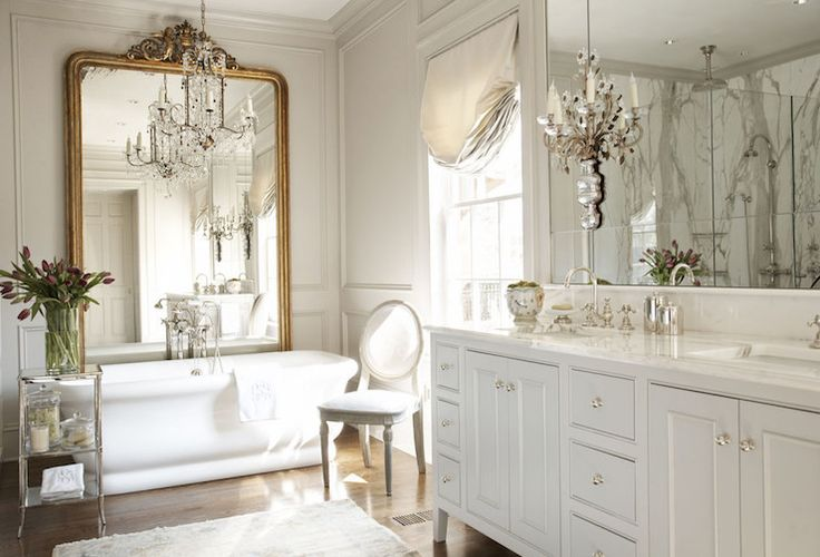 French master bathroom features a white double washstand with feet topped with a white marble framing his and her sinks under mirror illuminated by French sconces. Master bath boasts gray walls accented with gray trim moldings alongside a gilt floor mirror leaning against a wall placed in front of a freestanding tub under a chandelier paired with a polished nickel etagere and an oval back French chair