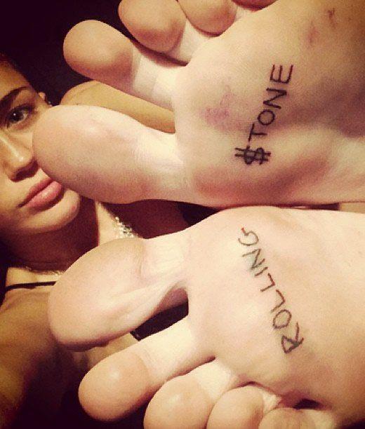 "Miley Cyrus' ""Rolling $tone"" Tattoos on Her Feet - http://www.popstartats.com/miley-cyrus-tattoos/feet-rolling-stone/"