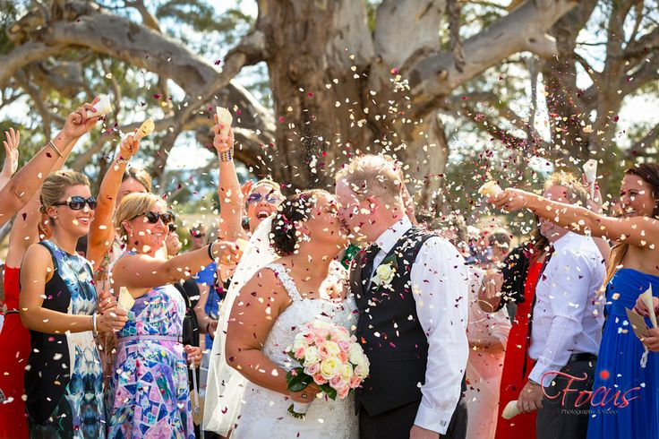 Happy guests throwing confetti and the beautiful couple kissing. Such a special and beautiful photography moment in any wedding.