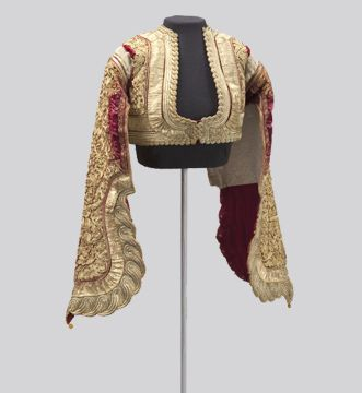 Short, fitted jackets were fashionable for men and women in 19th century Greece. The loose sleeves allow the wearer to move freely while dancing. Such jackets are characterized by gold embroidery on a dark velvet ground. Embroidering with metal thread is a long tradition in Greece that was profoundly influenced by centuries of Ottoman rule.