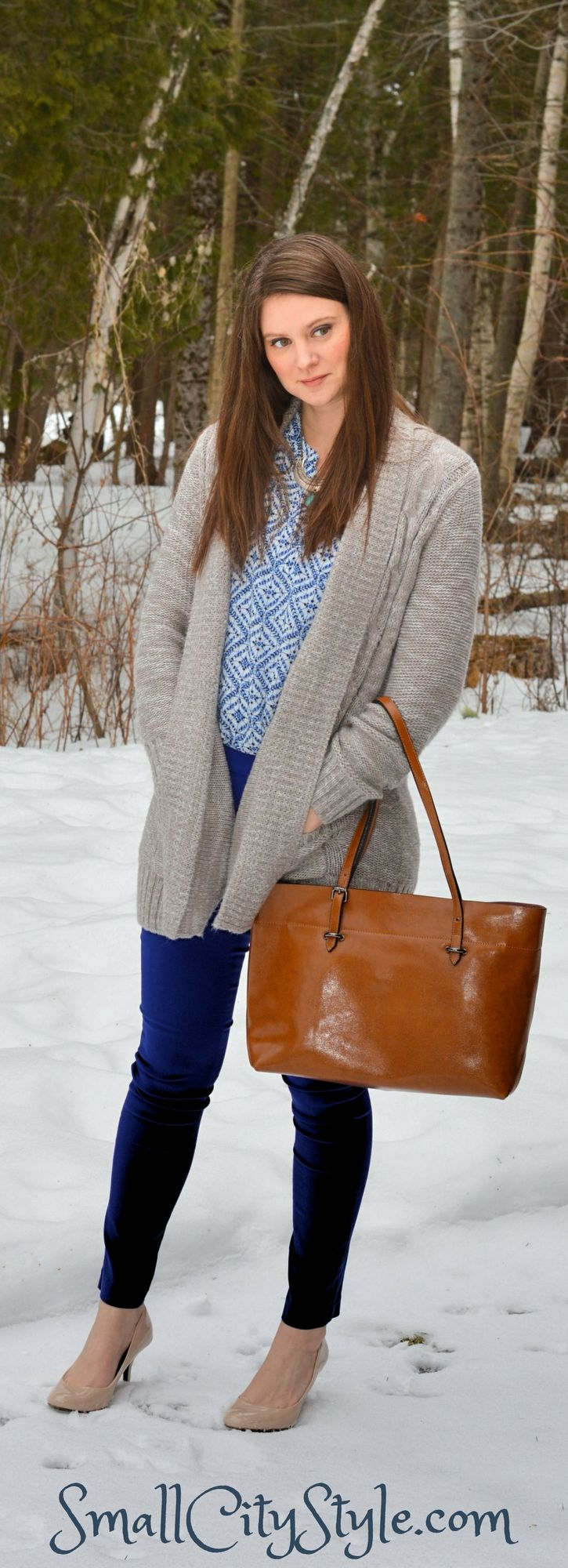 Women's winter outfit, cobalt blue pants, white and blue top, heavy knit cardigan, neutral pumps, brown leather tote.