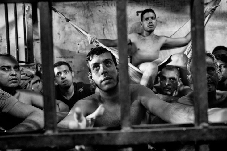 Prisoners inside a crowded cell at the Chacao municipal police station in eastern Caracas. There is no room to  sit and prisoners take turns resting on sheets tied to bars like hammocks.  Jails in Venezuela are seriously overcrowded with shortages of food and medicine. Because of the economic and political crisis, the number of prisoners grows daily as more Venezuelans are arrested for crimes, including mugging, kidnapping and murder, June 2016. <br><br>From <a…