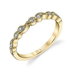 This elegant and whimsical wedding band in yellow gold features mixed shaped frames with milgrain edging encircling different sizes of luscious round brilliant diamonds in bezel and prong settings.  Whether paired with an elegant engagement ring or worn with a collection of your favorite stackable bands, this enchanting ring will enhance any style.  The total weight of this bewitching band is 0.16 carats.