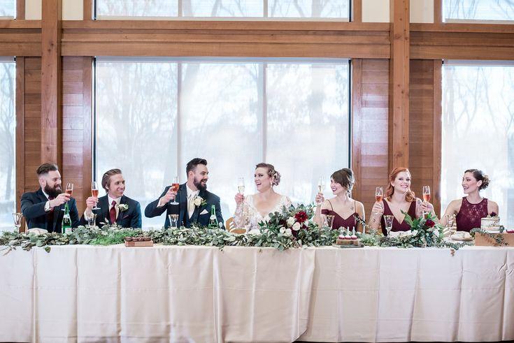 Head table floral decor designed by Minneapolis wedding florist Artemisia Studios at Silverwood Park. Photo by Iris Studios Photography (https://www.irisstudiosphoto.com/) #wedding #floraldecor #weddingdecor #headtable #bride #groom #bridesmaids #Burgundy #weddingstyle #winterwedding #flowers #artemisiastudios #minneapolisweddingflorist #saintpaulweddingflorist