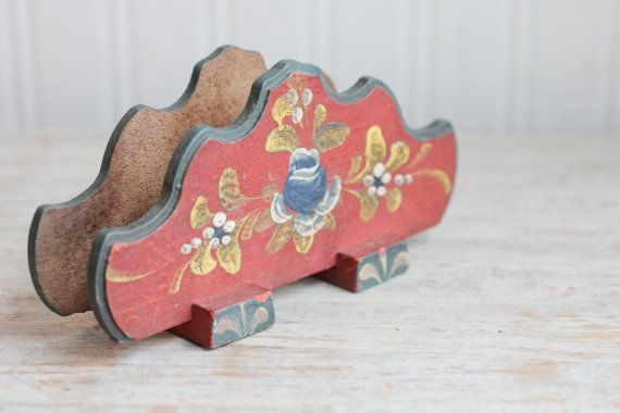 This vintage toleware napkin holder is made of wood. It is a Scandinavian folk art style and has decorative scalloped edges. The colors are a dark brick red with country blue, gold and white. Very nice vintage condition, read to give or use.  More vintage Scandinavian: https://www.etsy.com/shop/MollyFinds/search?search_query=scandinavian&order=date_desc&view_type=gallery&ref=shop_search