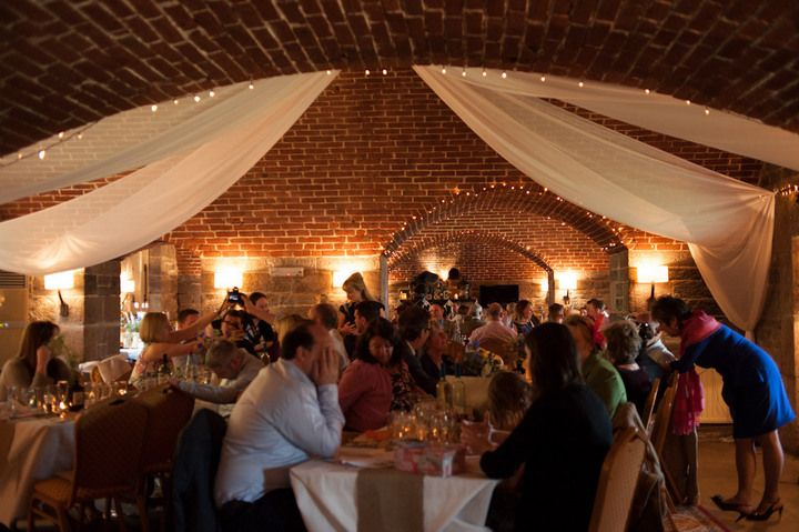 Chris and Sian's Travel Themed Cornish Cliff Top Wedding. By Toast of Leeds. The bustling grand hall at Polhawn Fort.