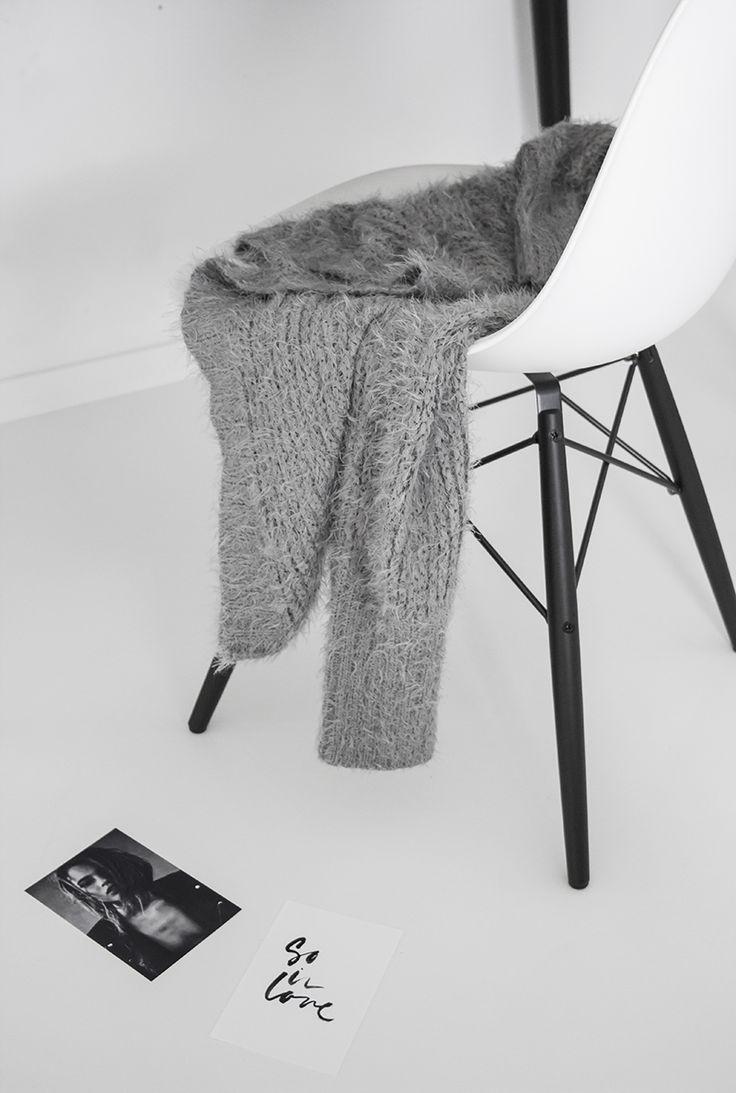white walls, white chair, grey sweater