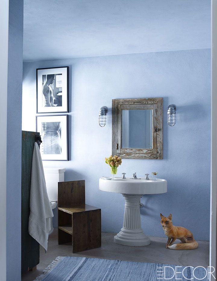 Banheiro com uma cadeira da coleção Huniford, fotografias de Nicholas, uma pia  antiga, luminárias antigas de navio. Um armário de remédios foi feito de madeira recuperada de um celeiro; as paredes são à prova d'água, e o piso é de concreto polido.  Fotografia: William Waldron.