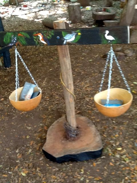 All-recycled material outdoor weighing scale decorated with pictures of birds which are seen locally.  Scales are made from calabashes.  Weights are recycled drinking water sachets filled with rice. #Playtime in Africa.