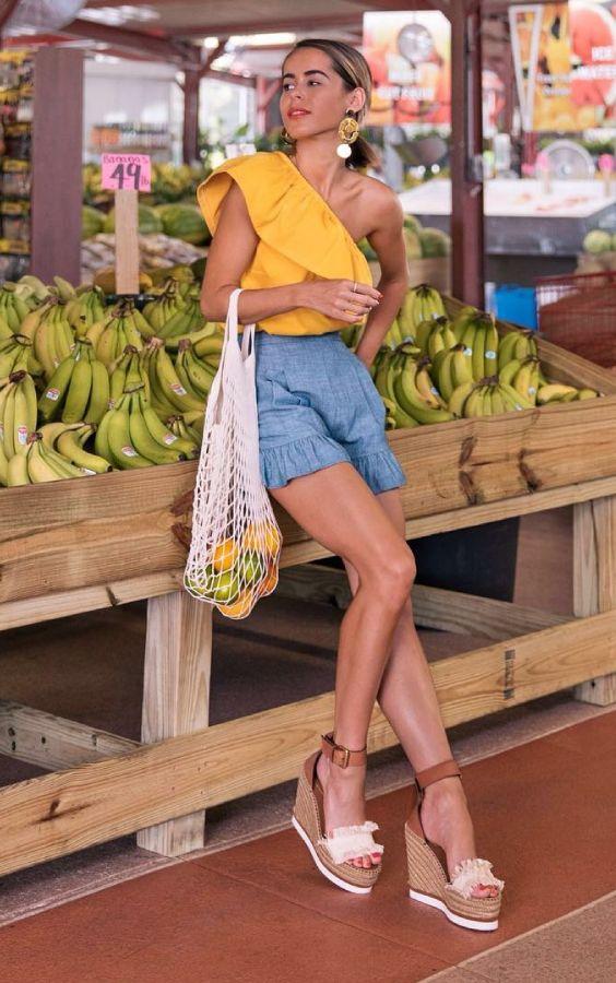 Como usar babados na próxima estação. Blusa assimétrica, um ombro só, amarela, shortinho jeans, espadrilha