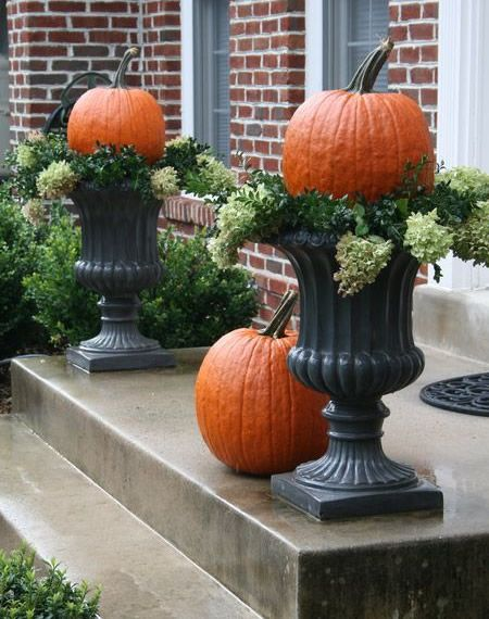 cute pumpkin topiaries in front porch urns
