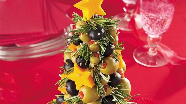 """Star-shaped cheese """"ornaments"""" adorn an edible evergreen fashioned from pimiento-stuffed and Kalamata olives."""