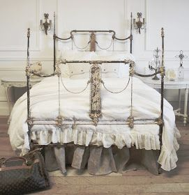 Vintage bed topped with bedding that looks vintage.