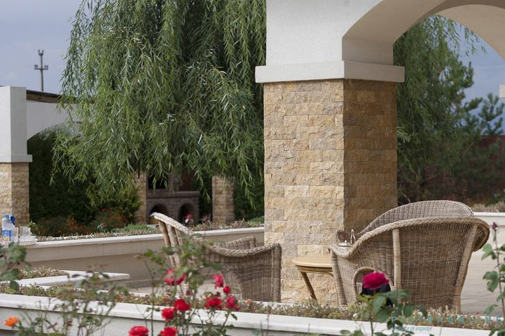 Pillar cladded with split face travertine. A terrace on a residential property in Prahova County, Romania.
