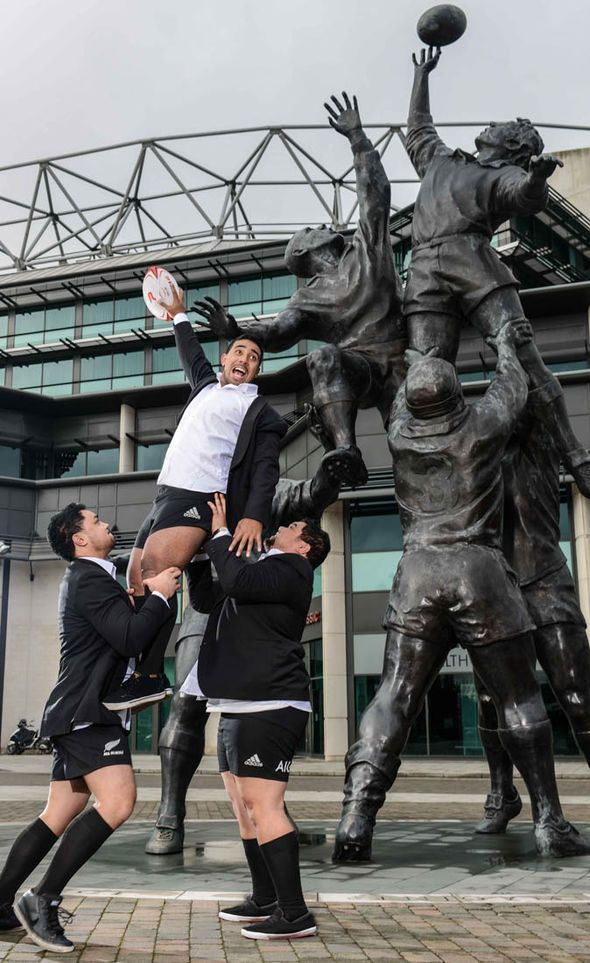 Sole Mio singers in front of rugby statue