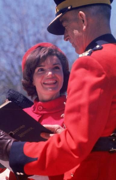 First Lady Jacqueline Kennedy smiling as Commissioner Harvison of the Royal Canadian Mounted Police presents her with their guest book after the Mountie's equestrian performance in her honor, Ottawa, Canada, May 1961.